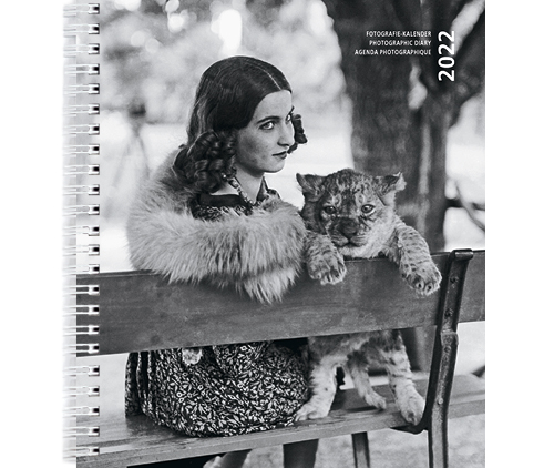 Coverbild Kalender 2022. Eine Frau mit einem Tigerbaby auf einer Bank